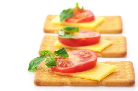 Three square crackers with slices of cheese, tomato and basil isolated on white background.