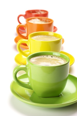 Four colorful cups with fresh coffee on white background.