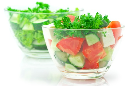 Two various salads of assorted vegetables in glass bowls isolated on white background.