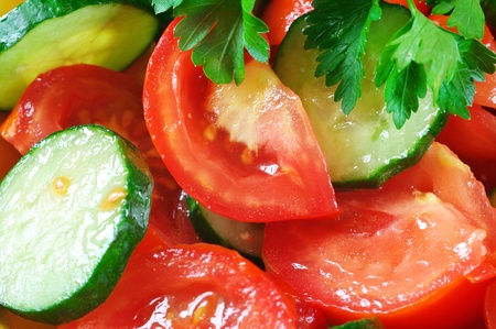 Close-up of fresh salad of tomatoes, cucumbers and parsley. Full frame.