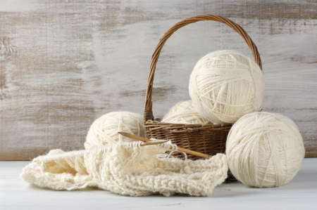 Natural woolen yarn and knitting on vintage wooden.