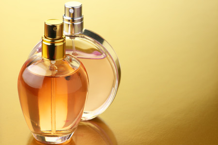 Two bottles of woman perfume on gold background with copy space.