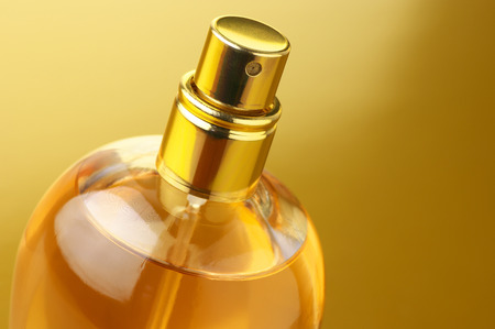 Bottle of woman perfume close-up on gold background.