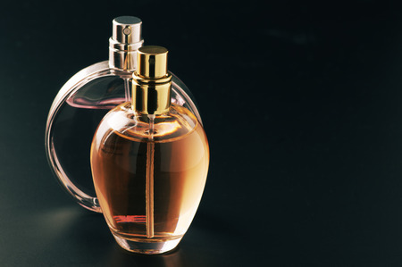 Two bottles of woman perfume on dark background with copy space.