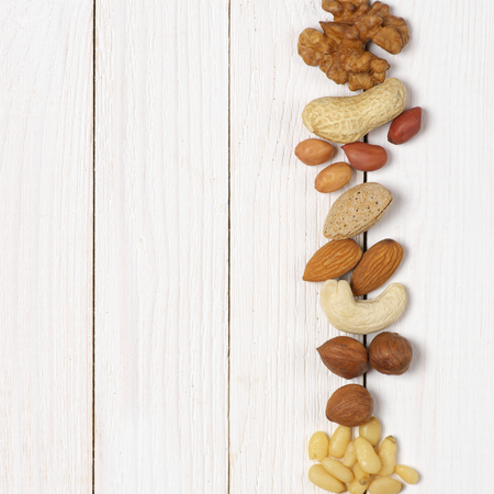 Variety of assorted nuts in row on white wood background with copy space. Top view point.