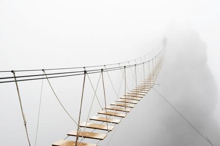 Fuzzy man walking on hanging bridge vanishing in fog.