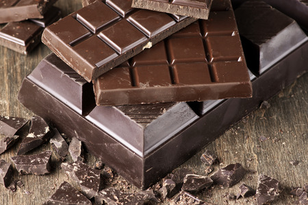 Assorted dark chocolate bars and chopped chocolate on vintage wooden background.