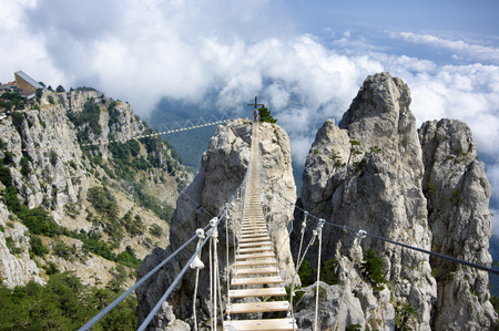 Hanging bridge in steep rocks with going man. Ai-Petri, Crimea.