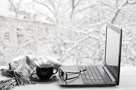 Foto de Cozy winter still life: laptop, glasses, cup of hot coffee and warm plaid on windowsill against snow landscape from outside. - Imagen libre de derechos