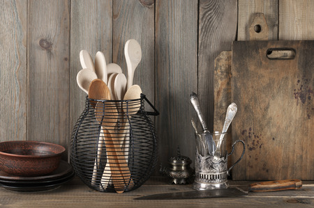 Photo pour Vintage rustic kitchen still life: silver glass holder with cutlery, ceramic dishware, wire basket with wood spoons and cutting boards against vintage wooden background. - image libre de droit
