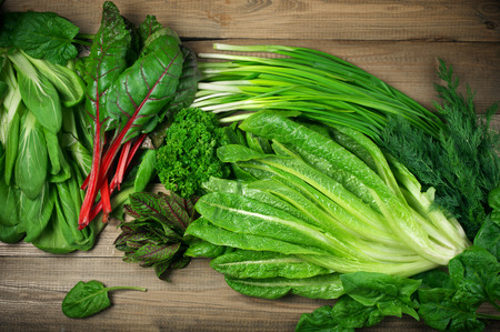 Photo pour Spring vitamin set of various green leafy vegetables on rustic wooden table. Top view point. - image libre de droit