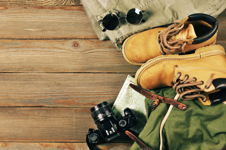 Foto de Travel accessories set on wooden background: old hiking leather boots, pants, backpack, map, vintage film camera and sunglasses. Top view point. - Imagen libre de derechos