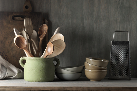 Photo pour Kitchen utensil set in rough handmade ceramic pot, crockery, cutting boards, grater, towel on wood shelf against rustic wooden wall. Low light. - image libre de droit