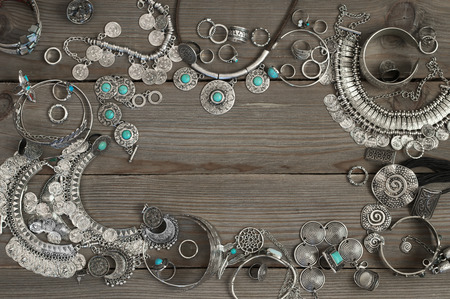 Photo pour Bohemian style silver jewelry set on grey old wooden background. Top view point. - image libre de droit