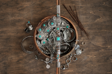 Photo pour Boho style rings set on wooden sticks and bowl with assorted bohemian chic silver jewelry on wood background with copy space. Top view point. - image libre de droit