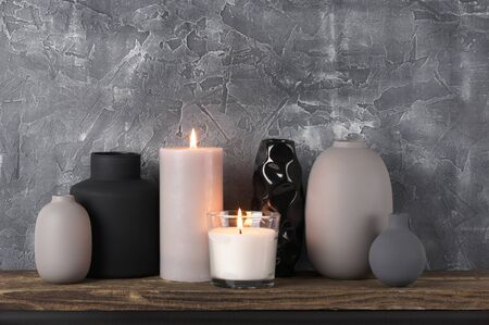 Photo pour Neutral colored vases and burned candles on distressed wooden shelf against rough plaster grey wall. Home decor. - image libre de droit