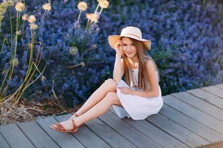 Photo pour Nice little girl in white dress sitting in the park - image libre de droit