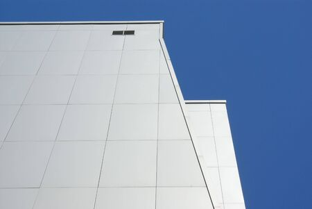 Modern front system. The many-storeyed building revetted with metal panels