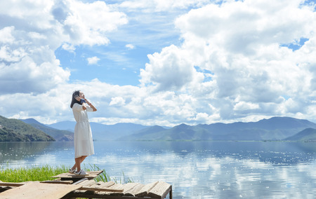 Single young Chinese woman in white long skirt stands by Lugu lake