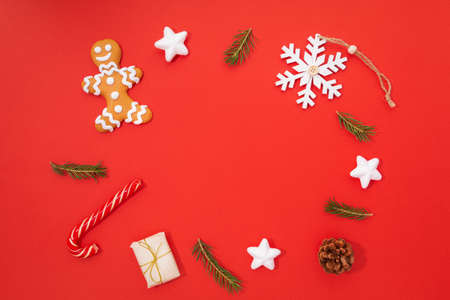 Photo pour A Christmas composition consisting of a gingerbread man, gifts, a Christmas tree, a snowflake and a lollipop is located on a red background. New Year and Christmas concept. There is a place for text. - image libre de droit
