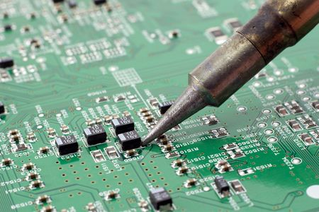 Technician repairing electronic circuit board with soldering iron.