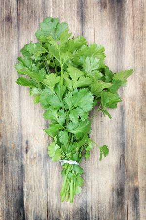 Fresh, organically grown coriander or cilantro on a wooden chopping board.