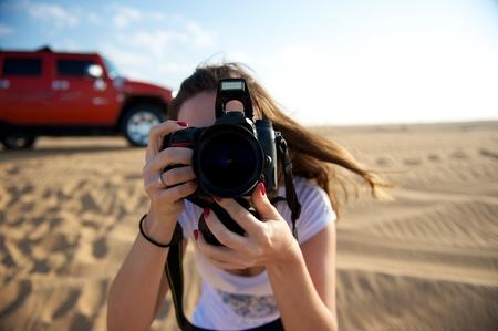 Pretty young woman taking photo in the Dubai Desert, United Arab Emirates