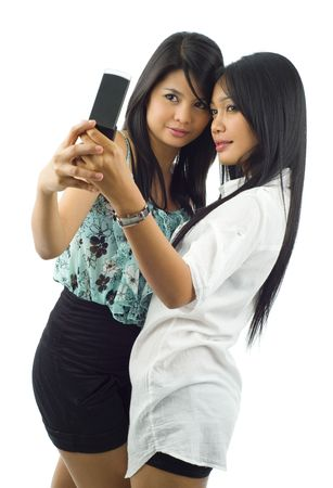 two asian women taking a picture of themselves with a mobile phone, isolated on white