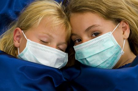two girls with protective masks sick in bed