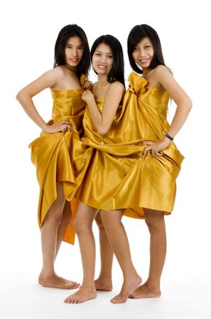three young nude asian women covered in silk fabric, isolated on white background