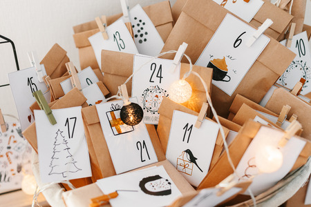 Photo pour Advent calendar waiting for Christmas. Basket with envelopes with numbers and tasks for children standing on cabinet - image libre de droit