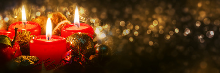 Advent candles with christmas decoration in atmospheric light.