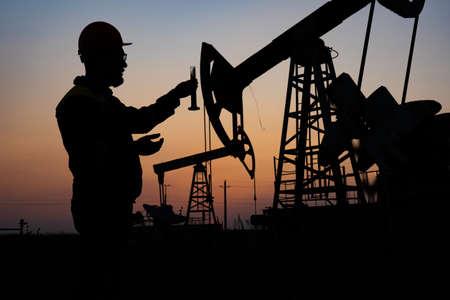 Foto de Silhouette of a chemical engineer taking a sample of crude oil against the background of oil pumps. - Imagen libre de derechos