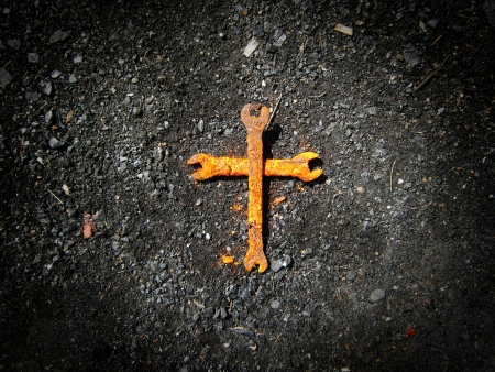 Rusty wrench cross on the coal background