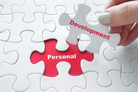 Close up of girl's hand placing the last jigsaw puzzle piece with word Personal Development