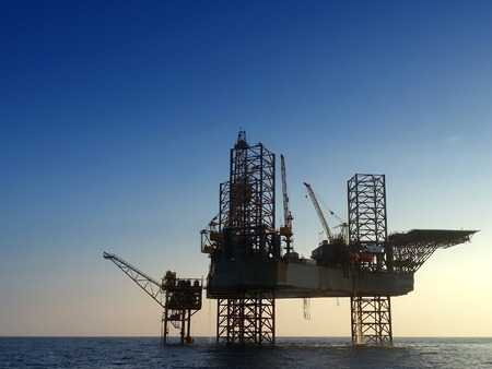 silhouette offshore oil rig drilling platform and small ship with blue sky early morning