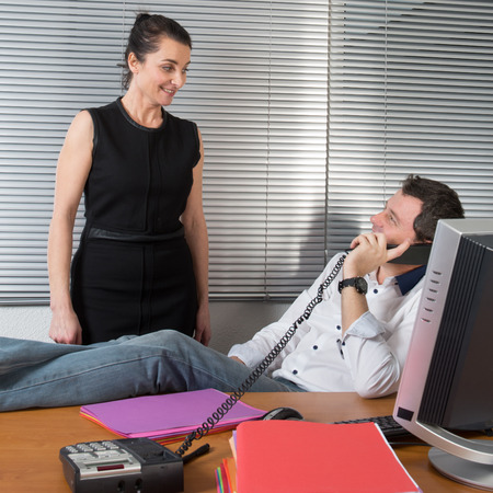 Photo pour business man relaxing at office desk and talking on mobile phone - image libre de droit