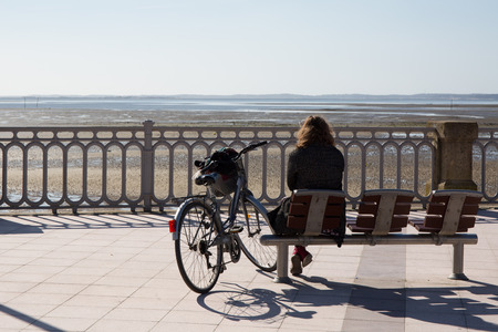 Photo pour A rear view of a woman sitting on a bench at sea side - image libre de droit