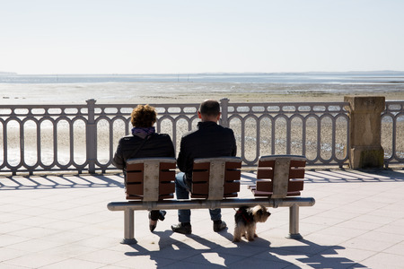 Photo pour A rear view of people sitting on a bench at sea side - image libre de droit