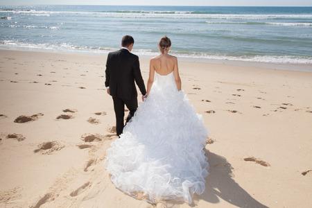 Photo pour Beautiful couple on the beach in wedding dress - image libre de droit