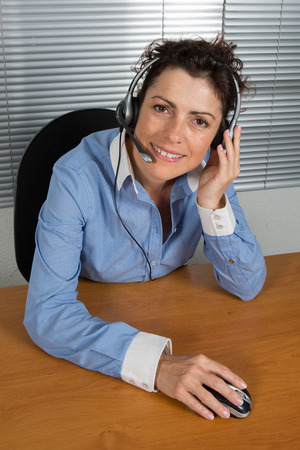 Smiling and happy businesswoman in a call center office