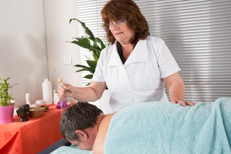Female therapist doing head massage on man in the spa salon.