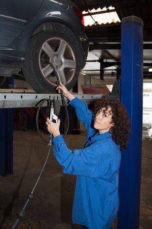 Woman as female car mechanic working on an auto in a workstation