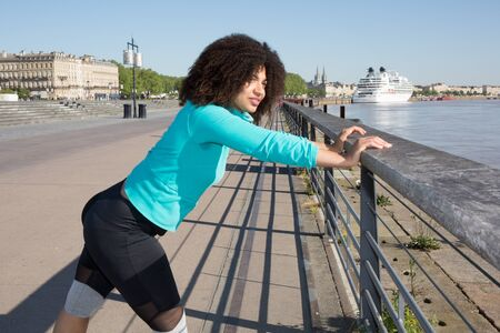 young curly woman practicing sport along the river