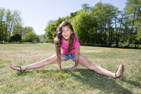 girl child plays to do gymnastics in the park