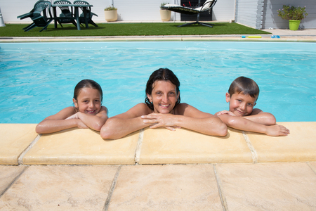 mother daughter and son pleasure on pool at home in summer