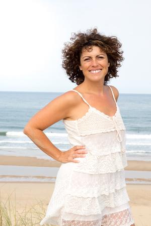 Pretty woman in white dress on the beach