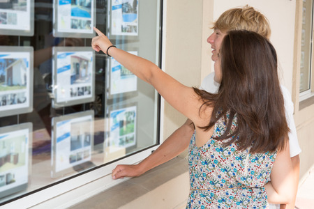 Photo pour Side view young couple looking window display at real estate office in strret - image libre de droit