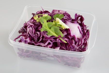 healthy vegetarian salad with red cabbage chopped in the plastic take away box