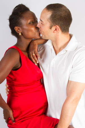 Portrait of young black american pregnant and her white male husband kissingの写真素材
